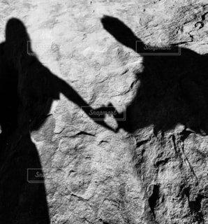 ハートをかたどるカップルの手の影の写真・画像素材[1588738]