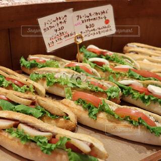 木製のまな板の上に座っているサンドイッチの写真・画像素材[2278199]