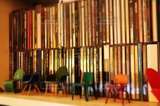本の棚の前に座っている椅子の写真・画像素材[1603968]