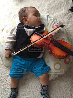 寝相アート。バイオリンを弾く赤ちゃんの写真・画像素材[1615550]