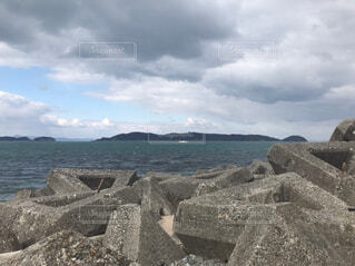 水の体の横にある岩のビーチの写真・画像素材[1803238]