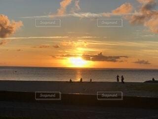 ビーチでの背景の夕日に人々 のグループの写真・画像素材[1600369]