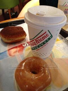 コーヒー カップの横に座っているドーナツの写真・画像素材[1601756]