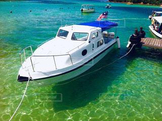 水の体の横に座っている青と白のボートの写真・画像素材[1616517]
