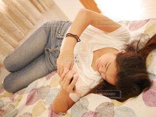ベッドの上でスマホをいじる女の子の写真・画像素材[1831694]