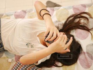 ベッドの上でスマホをいじる女の子の写真・画像素材[1831696]