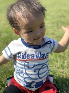 草の中に座っている小さな男の子の写真・画像素材[1607271]
