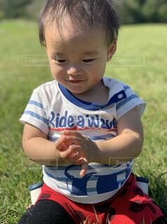 芝生に座っている小さな男の子の写真・画像素材[1607273]
