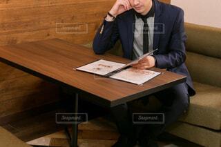 木製のテーブルの上に座っている男の写真・画像素材[2682087]