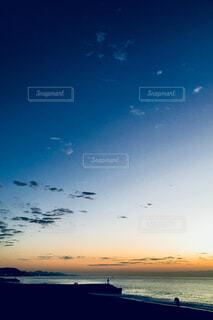 海からの日の出と釣り人の写真・画像素材[902220]
