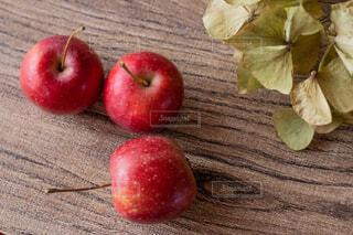 木製テーブルの上に座っている赤いりんごの写真・画像素材[1620362]