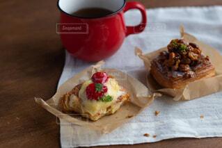近くのコーヒー カップの横にあるテーブルの上に食べ物のアップの写真・画像素材[1836929]