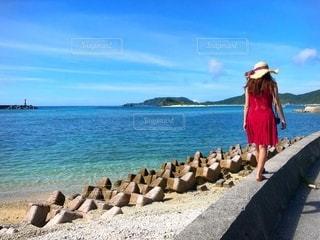 海岸沿いを散歩する赤いワンピースの女性の写真・画像素材[3491477]