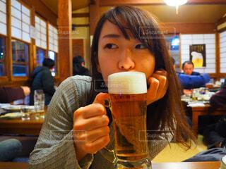 テーブルの上のビールのグラスを飲む女性の写真・画像素材[1619120]