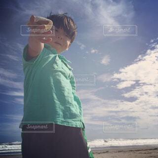 ビーチで貝殻を渡す男の子の写真・画像素材[1620526]