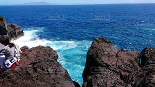 岩のビーチに立っている人の写真・画像素材[1622700]