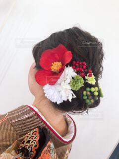 赤い花を付けている女性の写真・画像素材[2080646]