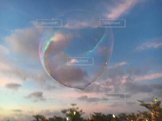 夕暮れ時の空に浮かぶシャボン玉の写真・画像素材[1645843]