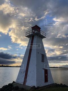 水の体の横にある大きな灯台の写真・画像素材[1651490]
