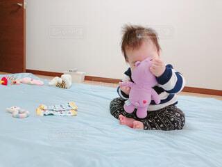 ベッドの上に座っているテディー ・ ベアを保持している小さな男の子の写真・画像素材[1704538]