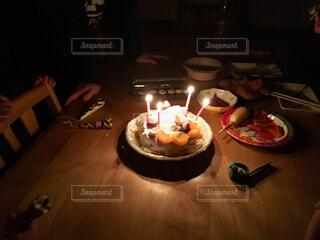 キャンドルとバースデー ケーキでテーブルに座っている人の写真・画像素材[1664682]