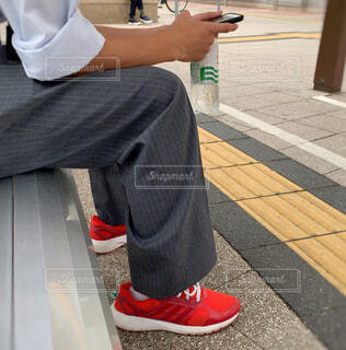 ベンチに座ってスマホいじり📱の写真・画像素材[2643246]