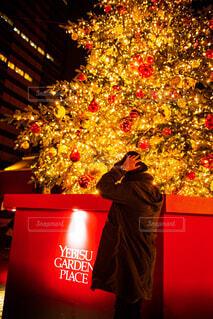 クリスマス ツリーの前に立っている人の写真・画像素材[1656437]
