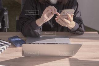 ラップトップを使用してテーブルに座っている人の写真・画像素材[1823685]