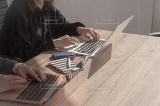 ラップトップ コンピューターを使用してテーブルに座っている人の写真・画像素材[1823687]