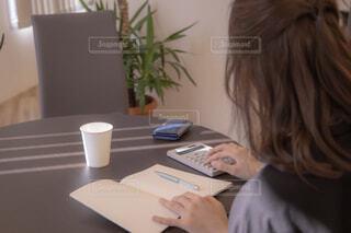 ラップトップを使用してテーブルに座っている人の写真・画像素材[1823695]