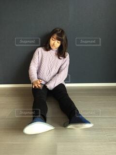 床の上に座って携帯をしている女性の写真・画像素材[1730333]