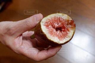 半分食べた果物を持つ手の写真・画像素材[2427471]