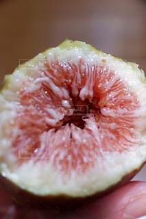 半分食べた果物を持つ手の写真・画像素材[2427476]