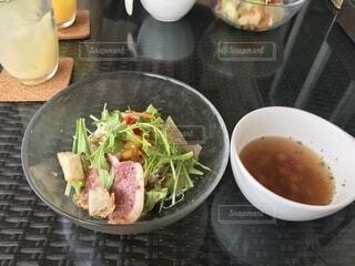 テーブルの上の皿の上に食べ物のボウルの写真・画像素材[1688971]
