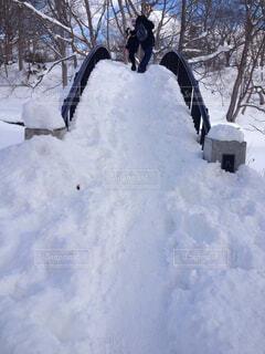 雪をスノーボードに乗る男覆われた斜面の写真・画像素材[1714157]