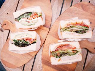 木製のテーブルの上にサンドイッチの写真・画像素材[1679237]