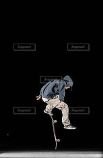 夜にスケート ボードに乗っている間は空気を通って飛んで男の写真・画像素材[1681457]