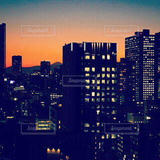 夕焼けの空にビルのシルエットの写真・画像素材[1681878]