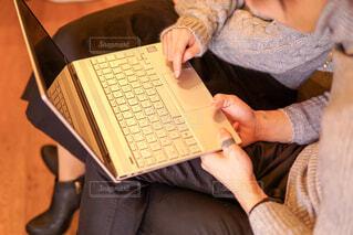 ラップトップ コンピューターを使用してテーブルに座っている人の写真・画像素材[1809263]
