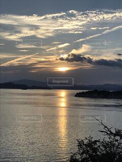 沈む夕日と飛行機雲の写真・画像素材[1687359]