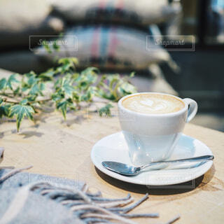 カフェテーブルの上のラテアート付きコーヒー カップの写真・画像素材[1687542]