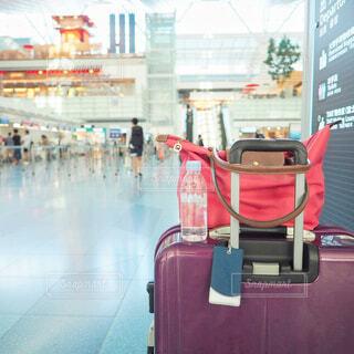 空港でスーツケースを持って出発を待つの写真・画像素材[1714884]