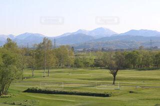 山が背景にある大きな緑の野原の写真・画像素材[2142465]