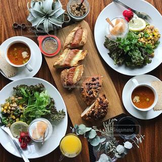 テーブルの上の皿の上に食べ物のボウルの写真・画像素材[1295389]