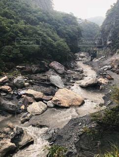山の中腹に木と岩の多い川の写真・画像素材[1694139]