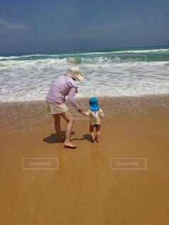 ビーチの砂の上に立っている親子の写真・画像素材[1694814]