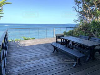 水の体の隣に座っている木製のベンチの写真・画像素材[3381643]