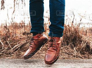 草の中で立つ革靴の写真・画像素材[1694248]