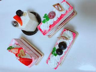 テーブルに赤と白のケーキの写真・画像素材[1700317]