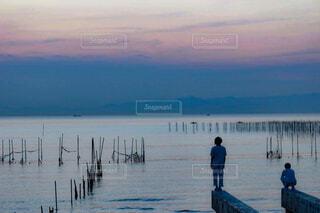 水の体の横に立っている人のグループの写真・画像素材[1712493]